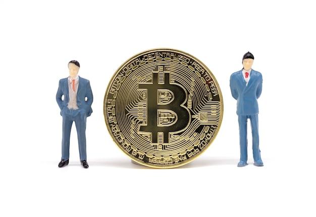 Juguete empresario y bitcoin sobre fondo blanco