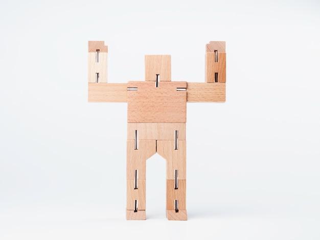 Juguete de madera, robot de bloques geométricos manos arriba con gesto de poder fuerte que se encuentran aisladas sobre fondo blanco, estilo minimalista.