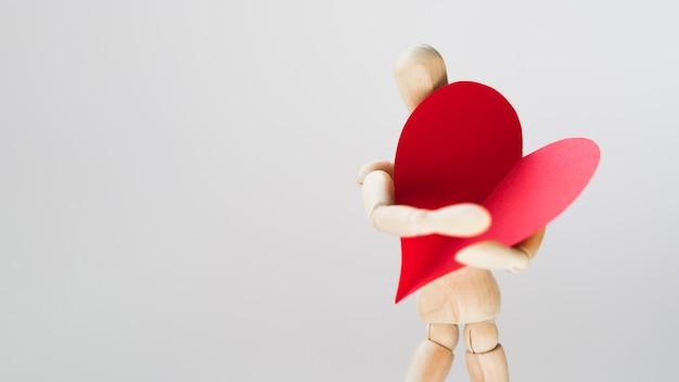 Juguete manequin sosteniendo corazón con espacio de copia
