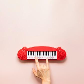 Juguete de mano y piano sobre fondo rosa