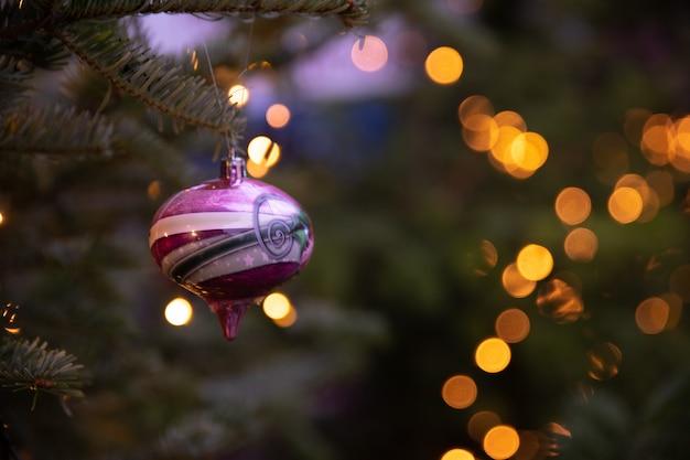 Un juguete de navidad multicolor colgando de una rama de abeto verde y bokeh amarillo en el fondo