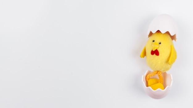 Juguete pollo pequeño en cáscara de huevo en mesa