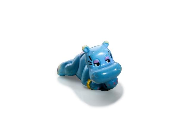 Un juguete de una sorpresa más amable., el hipopótamo azul yace boca abajo sobre un fondo blanco.