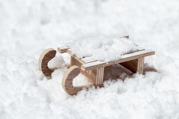 Juguete trineo de madera sobre la nieve con espacio vacío. concepto para año nuevo o feliz navidad. fondo de vacaciones de invierno.