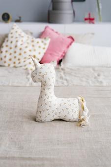 Juguete de unicornio suave en la cama en el dormitorio
