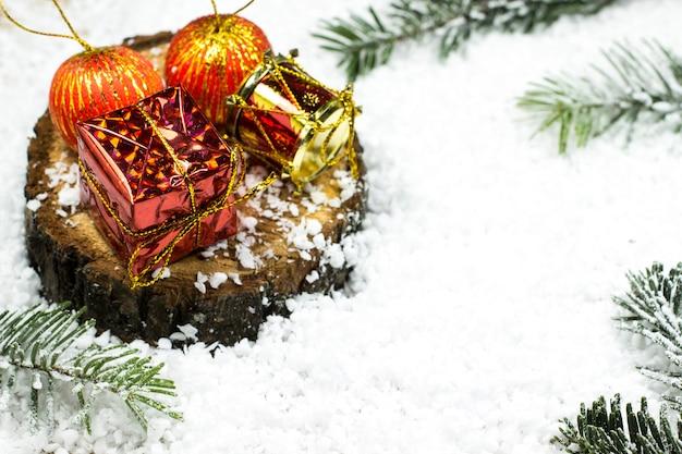 Juguetes de año nuevo en un tocón entre la nieve y las ramas de abeto