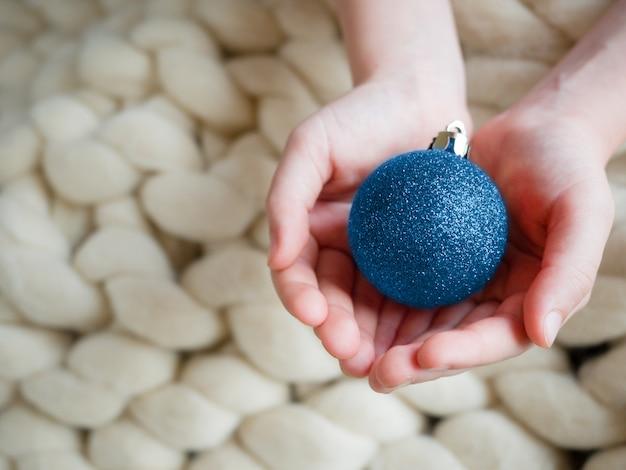 Juguetes de árbol de navidad como bola azul en manos en vista superior de lana