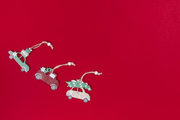 Juguetes en el coche del árbol de navidad sobre un fondo rojo.