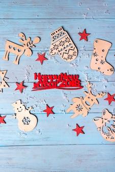 Juguetes colgantes de madera y feliz navidad saludo pequeñas letras rojas