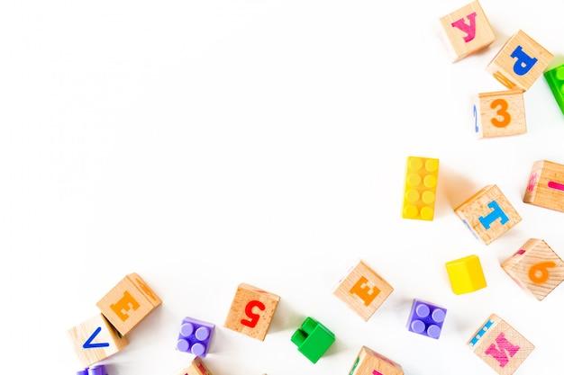 Juguetes coloridos del bebé en el fondo blanco. marco del desarrollo de bloques de madera, automóviles y rompecabezas.