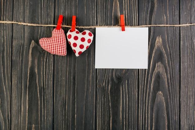 Juguetes de corazon colgando de una cuerda con tarjeta en blanco