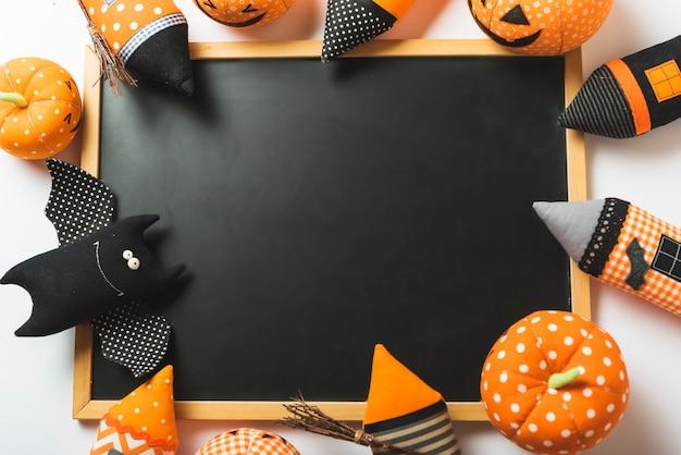 Juguetes de halloween suaves alrededor de la pizarra
