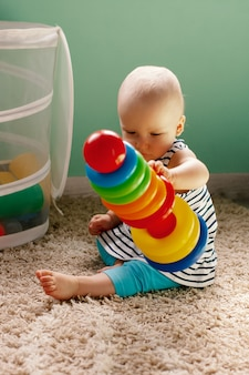 Juguetes lógicos educativos para niños. el niño recoge la pirámide de colores. juegos para el desarrollo del niño.