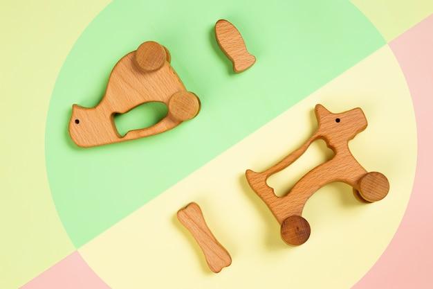 Juguetes de madera pingüino con pescado, perro con un hueso sobre fondo aislado rosa, verde y amarillo.