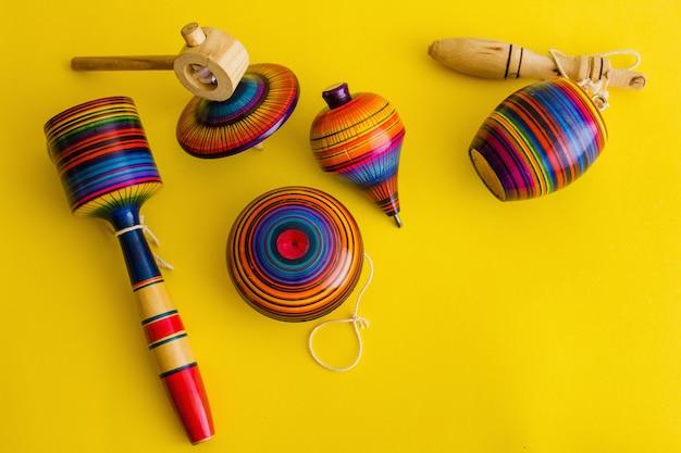 Juguetes mexicanos de madera, balero, yoyo y trompo en méxico sobre un fondo amarillo.