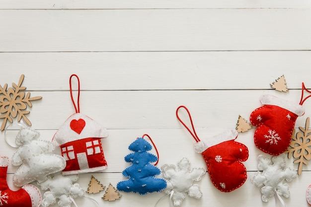 Juguetes de navidad caseros para familias con niños sobre fondo blanco de madera. endecha plana con decoración de año nuevo