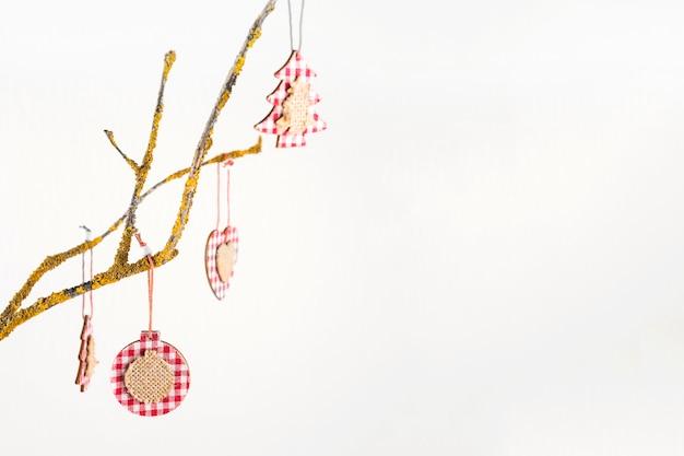 Juguetes de navidad colgando de la rama de un árbol.