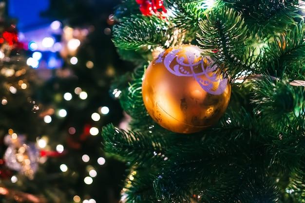 Juguetes de navidad y guirnaldas en el árbol de navidad. de cerca