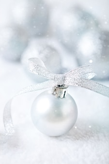Juguetes de navidad de plata sobre un fondo claro.
