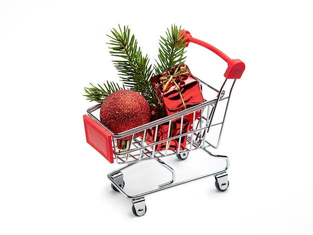 Juguetes de navidad, regalos y rama de abeto en la cesta del comprador. carrito de compras completo.