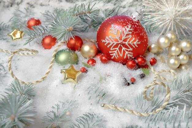 Juguetes navideños y decoraciones en ramas de abeto cubiertas de nieve