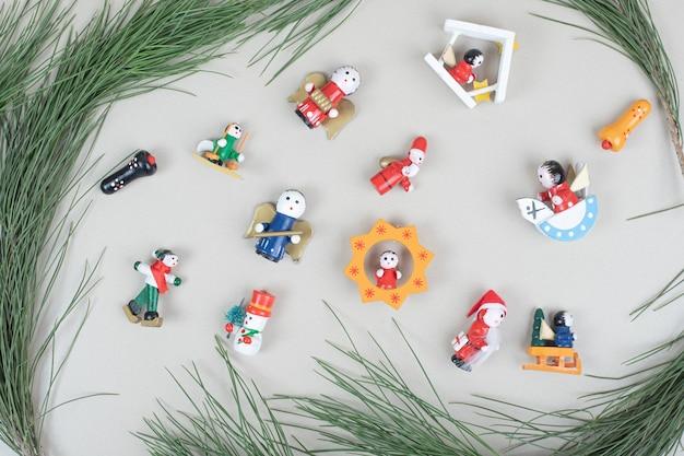 Juguetes navideños y rama en superficie beige.