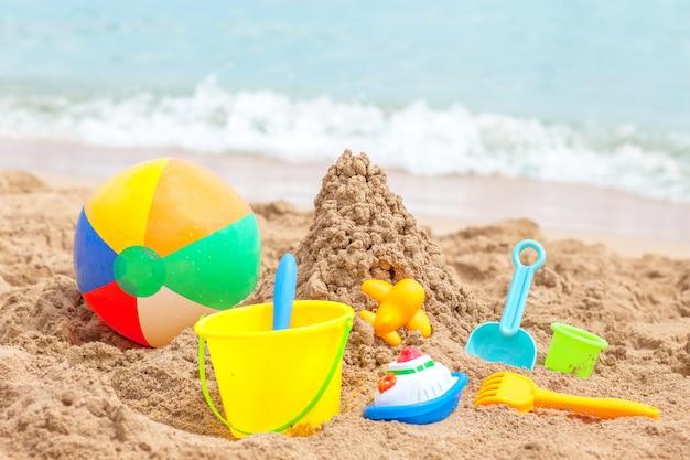 Juguetes para niños areneros contra el mar y la playa