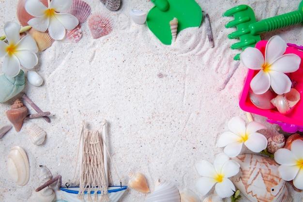 Juguetes para niños con conchas de mar y flores de plumeria sobre fondo de arena