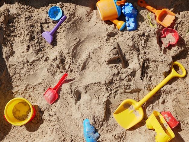 Juguetes para niños esparcidos en el arenero