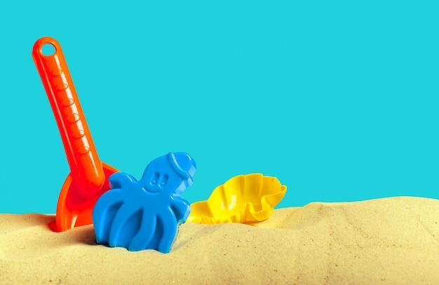 Juguetes de plástico para niños en la playa de arena