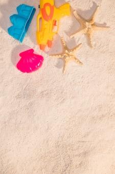 Juguetes de playa y estrellas de mar sobre arena.