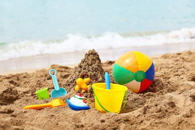 Juguetes de playa para niños: cubos, pala y pala en la arena en un día soleado