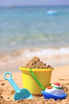 Juguetes de playa para niños con cubos, pala y pala sobre arena.