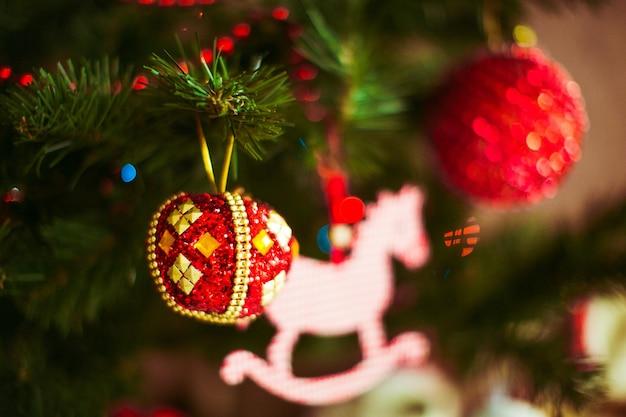 Juguetes rojos cuelgan de un árbol de navidad