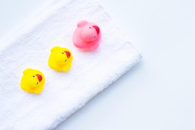 Juguetes rosados y amarillos del pato en la toalla blanca.
