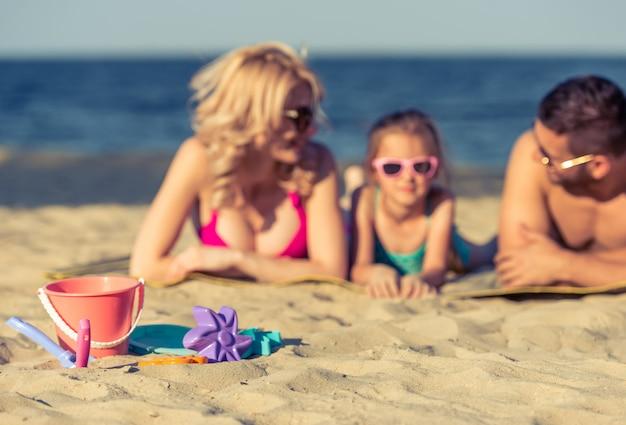 Juguetes tumbados en la arena, hermosa familia joven.