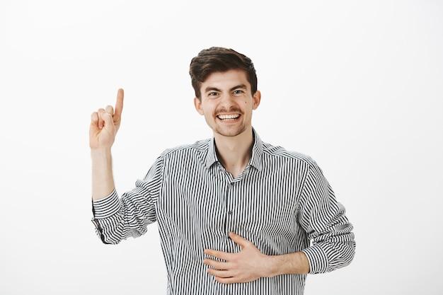 Juguetón amigo masculino positivo con bigote y lunares en la cara, levantando el dedo índice, sosteniendo la mano en el vientre, riendo a carcajadas al recordar un momento divertido durante la fiesta sobre una pared gris