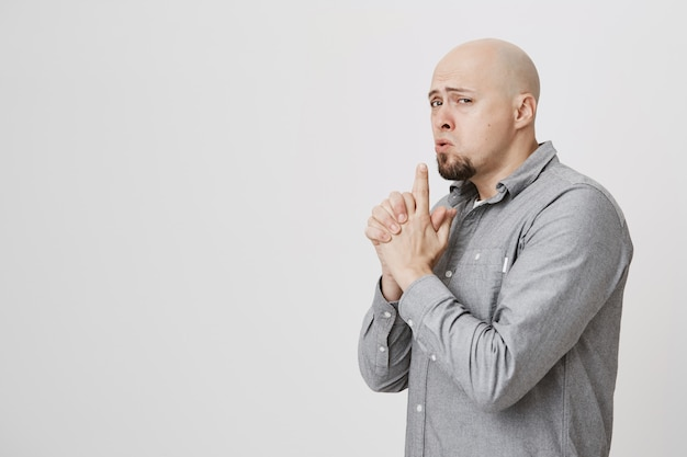 Juguetón descarado adulto calvo mostrar gesto de pistola, agente secreto imitando