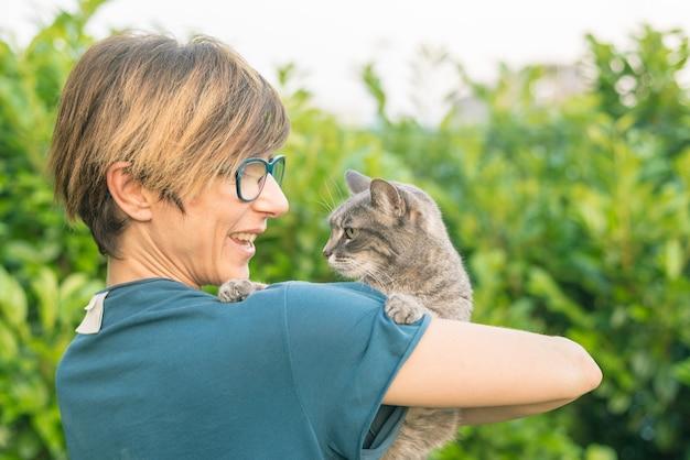 Juguetón gato doméstico sostenido y abrazado por una mujer sonriente con anteojos.