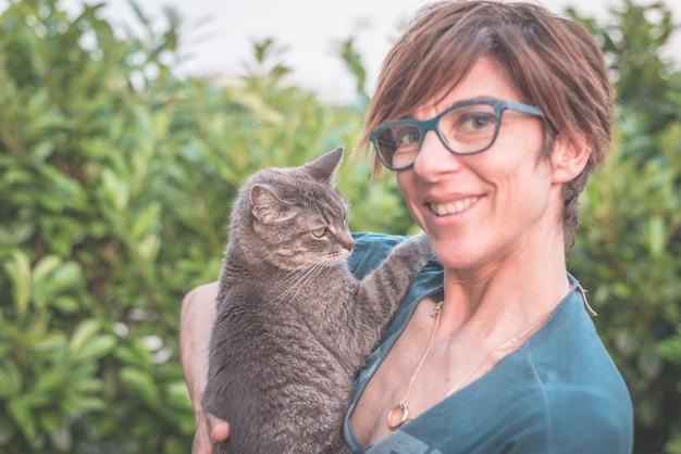 Juguetón gato doméstico sostenido y abrazado por una mujer sonriente con anteojos