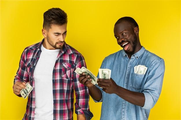 Juguetón hombre africano bromeando con un hermoso hombre europeo mientras se mantiene el dinero