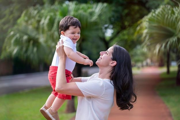 Juguetón joven madre brasileña levantando baby boy en segundo plano en el parque