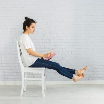 Juguetón libro de lectura de mujer en silla
