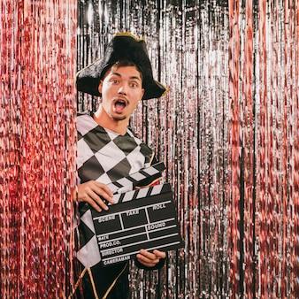 Juguetón masculino con pizarra de película en la fiesta de carnaval