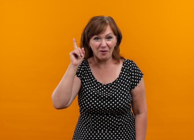 Juguetón mujer de mediana edad apuntando con el dedo hacia arriba en la pared naranja aislada con espacio de copia