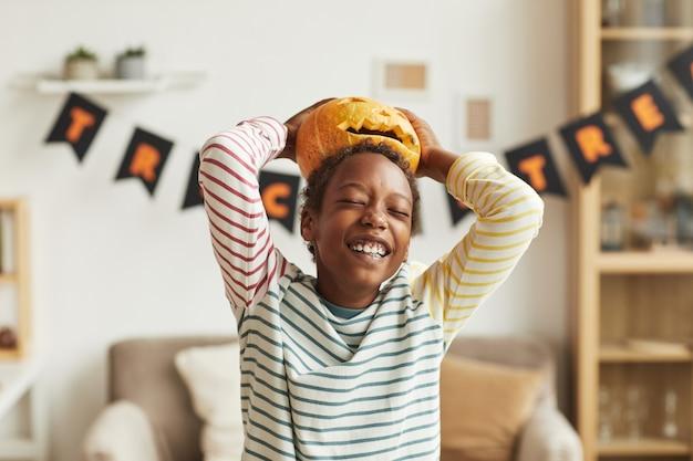 Juguetón niño afroamericano divirtiéndose con jack o 'lantern calabaza poniéndola sobre su cabeza, retrato medio
