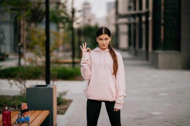 Juguetón retrato de mujer joven y bonita divirtiéndose en la calle