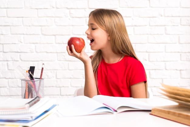 Juguetona colegiala mordiendo manzana