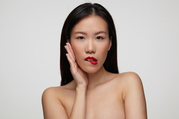 Juguetona joven hermosa mujer de cabello oscuro sosteniendo la palma levantada en su mejilla mientras muerde coquetamente su labio inferior, de pie sobre una pared blanca con los hombros desnudos