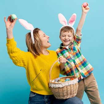 Juguetona madre e hijo mostrando huevos pintados